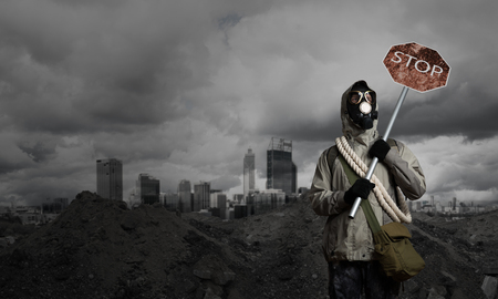 precaution: Stalker in gas mask with precaution stop signboard