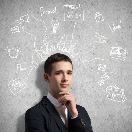 Young thoughtful man and sketches on wall Stock Photo