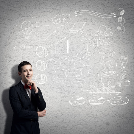 business mind: Young thoughtful man and sketches on wall Stock Photo