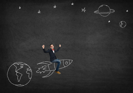 rise: Young businessman flying in sky on drawn rocket Stock Photo