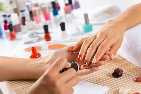 nail care: Woman in salon receiving manicure by nail beautician
