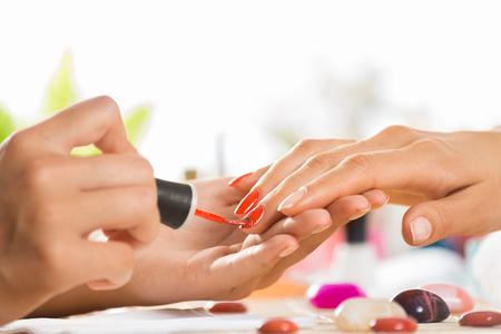 Frau im Salon Maniküre empfängt von Nagel Kosmetikerin