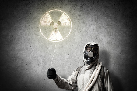 radioactivity: Man in respirator with radioactivity balloon in hands