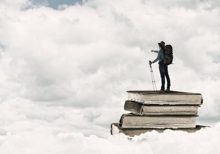 mochila de viaje: Excursionista hombre joven que se coloca en la pila de libros Foto de archivo