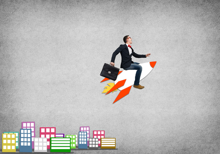 ride: Young businessman flying in sky on drawn rocket Stock Photo