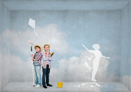 preteen boys: Cute boy and girl of school age painting wall with roller Stock Photo