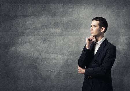 chin: Young thoughtful man with hand on chin Stock Photo