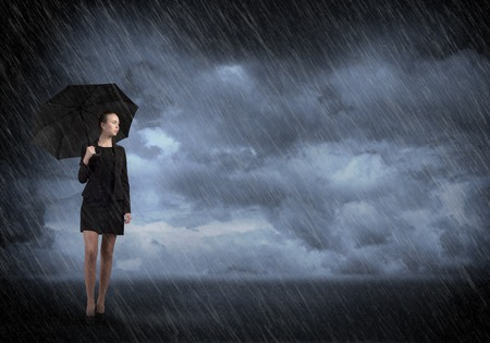 rain wet: Young businesswoman with umbrella standing in rain
