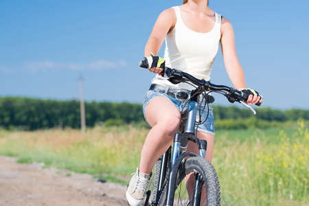 unrecognizable: Unrecognizable young woman in shorts riding bicycle outdoors Stock Photo