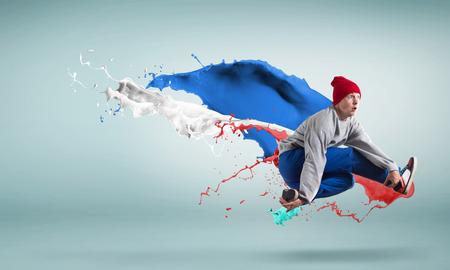 bailarin hombre: Bailarina de estilo moderno saltando sobre coloridas salpicaduras de pintura Foto de archivo