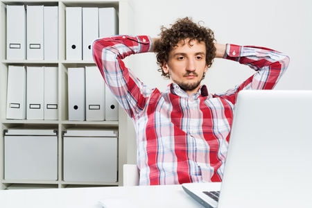 checked shirt: Young relaxed man in checked shirt in his office with hands on head
