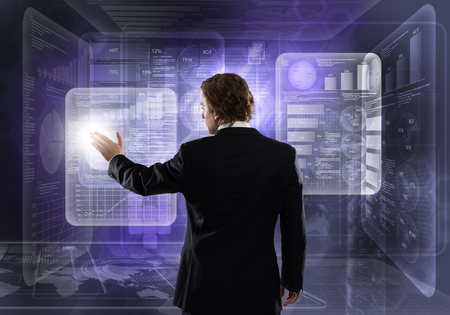 Rear view of businessman working with modern virtual panel