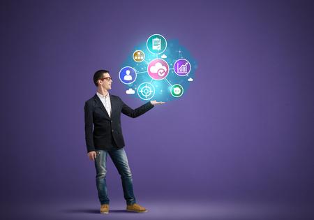 色の背景上手にソーシャルネットワー キングのアイコンを提示する若い男