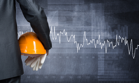 economist: Close up of businessman with helmet in hand and graphs at background Stock Photo