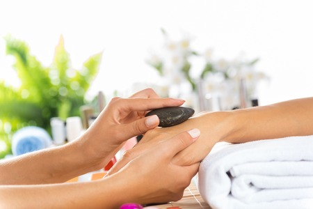 beautician: Woman in salon receiving manicure by nail beautician