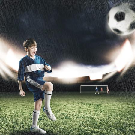 kicking ball: Excited boy football player at stadium kicking ball Stock Photo