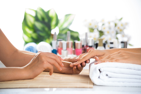 manicure: Woman in salon receiving manicure by nail beautician
