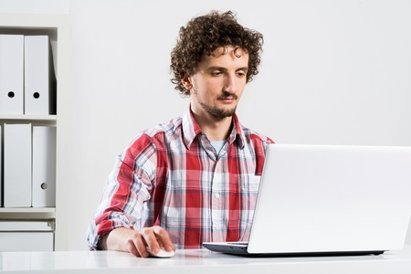 checked shirt: Young man in checked shirt typing on his notebook