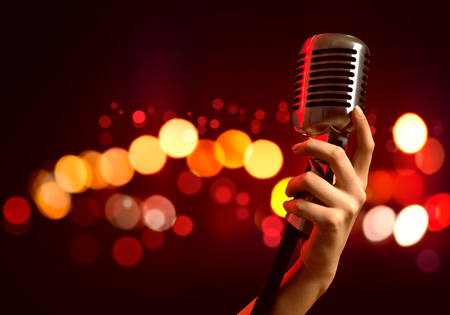 sound studio: Close up of female hand on blurred background holding microphone Stock Photo