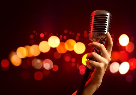 estudio de grabacion: Primer plano de la mano femenina en el micrófono borrosa fondo la celebración