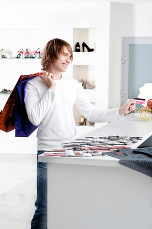 checkout counter: Young man at shopping mall checkout counter paying through credit card Stock Photo