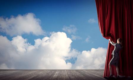 ステージの色のカーテンを開くビジネス スーツの若い女性