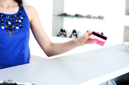 checkout counter: Young woman at shopping mall checkout counter paying through credit card Stock Photo