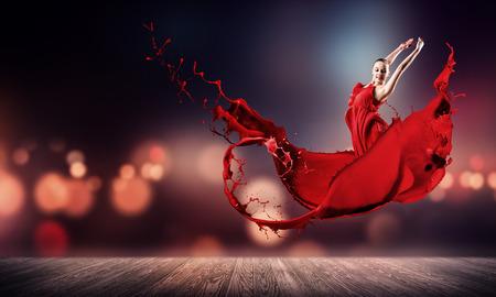 Bailarín de la mujer apasionada en vestido rojo y spalshes rojos Foto de archivo