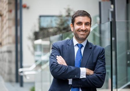 Hombre de negocios árabe feliz de pie con los brazos cruzados sobre el pecho Foto de archivo