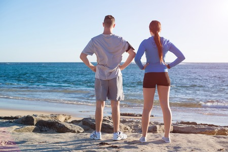 breath taking: Young active couple of joggers on beach taking breath