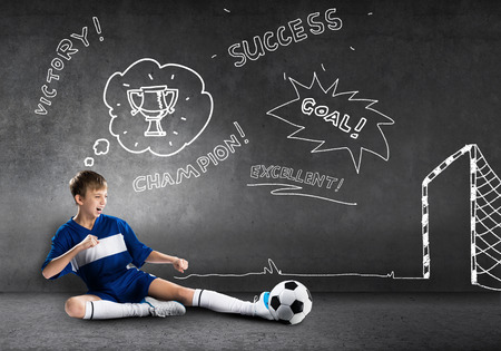 caucasians: School aged boy on sketched background playing football Stock Photo