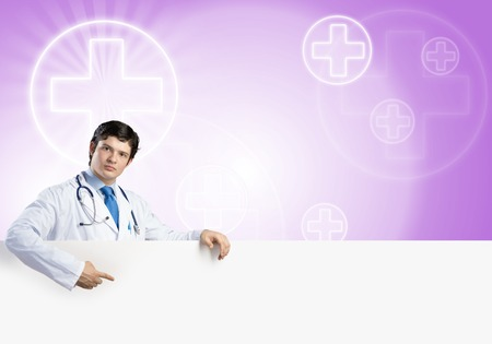 handsome doctor: Young handsome doctor holding white blank banner. Place your text