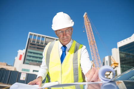 business project: Construction engineer in hardhat making notes in blueprint Stock Photo