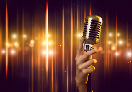 talents: Close up of female hand on blurred background holding microphone Stock Photo