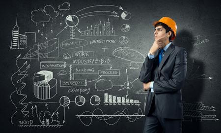 ingeniero: Joven ingeniero hombre pensativo en casco y bocetos en la pared