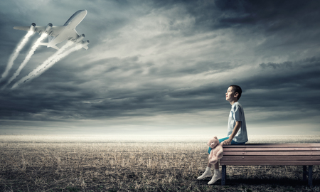 piloto: ni�o feliz ni�o sentado en el banco con el juguete del oso y el avi�n en el cielo Foto de archivo