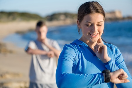 a check: Young couple on beach checking heart rate after run