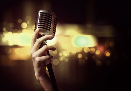 singer with microphone: Close up of female hand on blurred background holding microphone Stock Photo