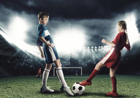 niño y niña: Dos adolescentes en edad escolar jugando al fútbol en el estadio