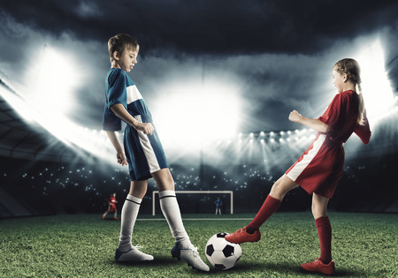 of boy and girl: Two teens of school age playing football on stadium