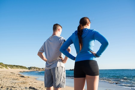 joggers: Young active couple of joggers on beach taking breath
