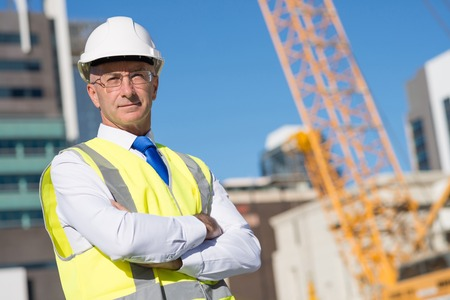 business suit: Confident construction engineer in hardhat with arms crossed on chest