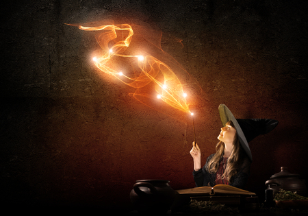 black magic: Little Halloween witch reading conjure from magic book above pot Stock Photo