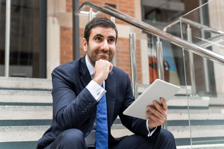 busy person: Thoughtful businessman sitting on steps with tablet pc