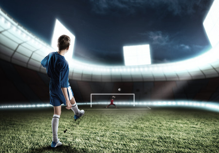 kicking ball: Kid boy football player on stadium kicking ball to gates