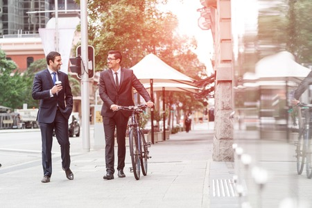 outdoors: Businessmen talking while walking with bicycle outdoors Stock Photo