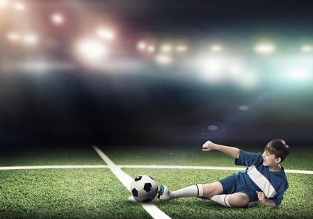 teen feet: Kid boy football player on stadium kicking ball Stock Photo