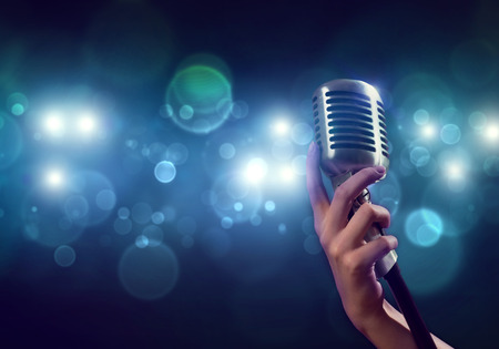 Close up of female hand on blurred background holding microphone Foto de archivo