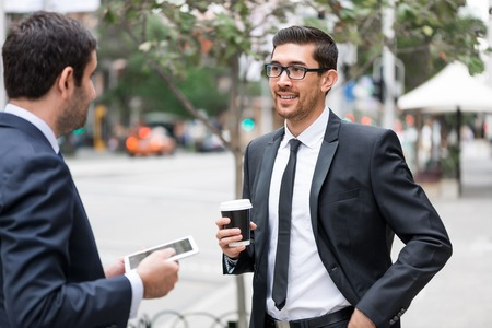 Two businessmen talking outdoors while taking coffee break