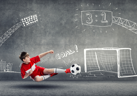 dreamer: School aged boy on sketched background playing football Stock Photo